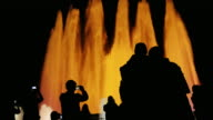 recognizable silhouettes of people in singing fountain in Barcelona. People watching the show, photographed fountain video