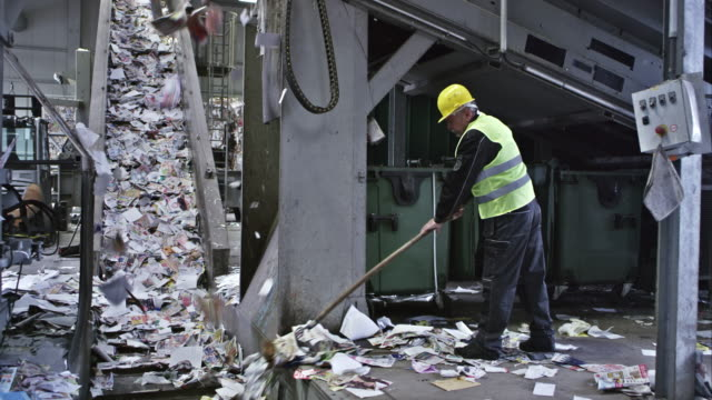 CS recycling facility worker sweeping paper onto conveyor belt video