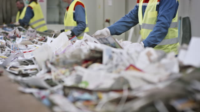 Recycling facility workers separating waste by hand on conveyor belt video