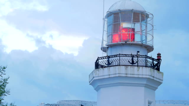 Red beacon light near the sea. Against the background of the morning sky in the clouds video