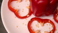 Red bell pepper cut by rings on a plate spinning. video