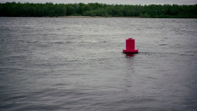 Red buoy on the river with a little excitement. Slow motion video