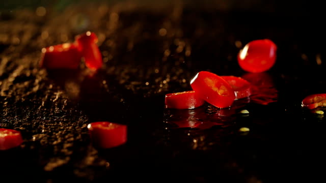Red Chili pepper falling in slow motion video
