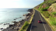 AERIAL: Red convertible car driving along coastal road above rocky shore video