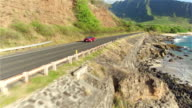 AERIAL: Red convertible car driving along coastal road above volcanic shore video