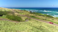 AERIAL: Red convertible driving along the coastal road in lush Hawaii island video
