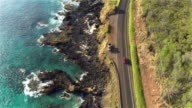 AERIAL: Red convertible driving on amazing coastal road above rocky ocean cliffs video