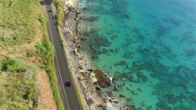 AERIAL: Red convertible driving on beautiful coastal road in volcanic island video