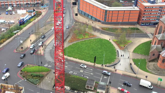 Red Crane looms over busy road junction watching traffic video