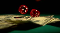Red dice falling on money, gambler playing game at casino, video