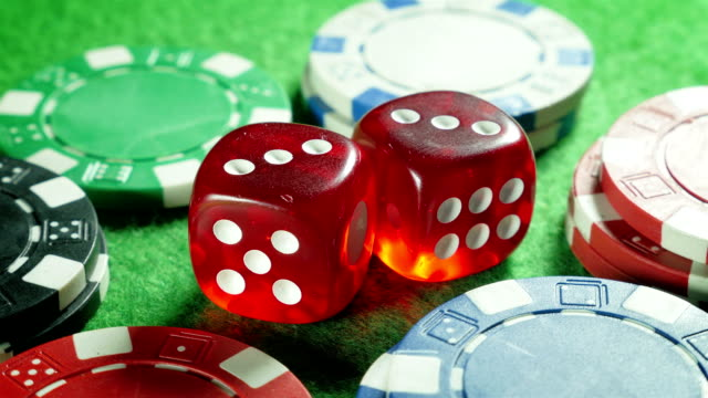 Red dices and casino chips on the green cloth background. Rotation. Double three. Backlight. video