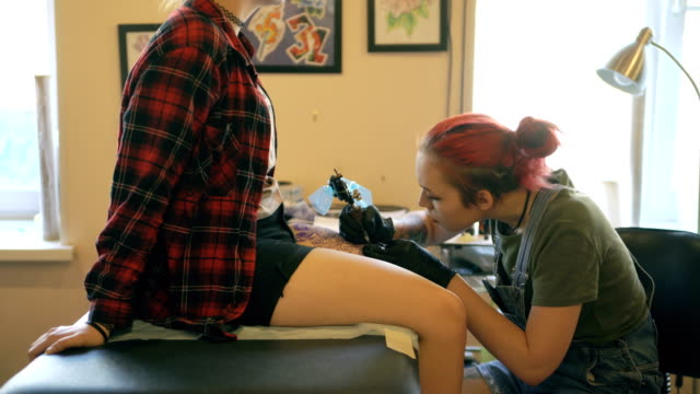 Red haired girl tattoo artist tattooing picture on lef of young girl client in studio video