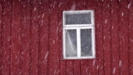 Red house wall with a window during snowfall video