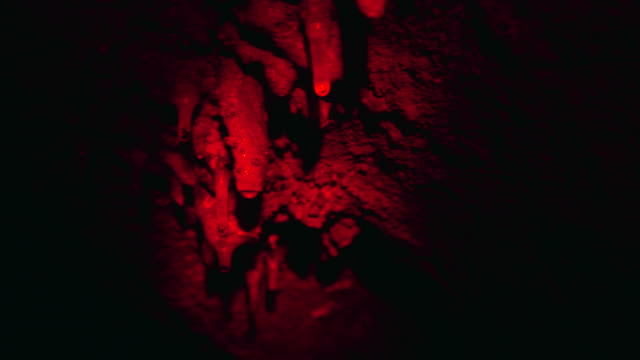 Red Light Sweeps Over Rock Formations in a Dark Cave video