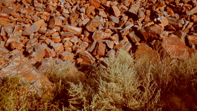 Red ore. Mountains of red ore. A girl in a swimsuit lies on a red ore video