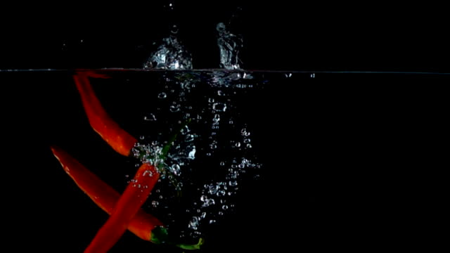Red pepper in water. Slow motion video