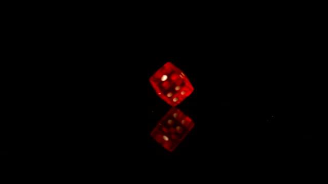 Red plastic dice revolving on black background video