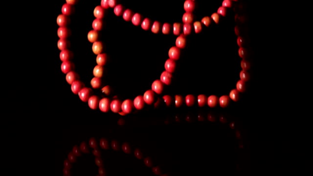 Red prayer beads falling on black background video
