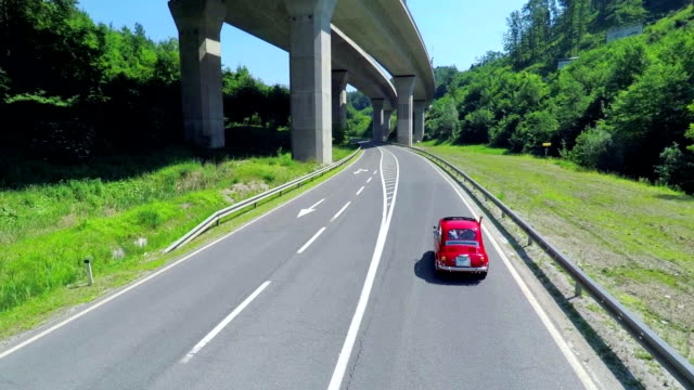 Red retro car driving uphill under a viaduct video