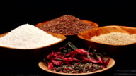 Red rice,millet grains,tapioca pearls in small bowls and a pile of dried chili video