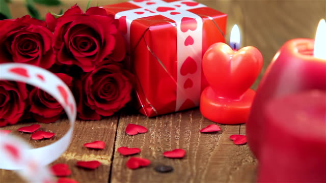 Red roses and gift box on wooden background video