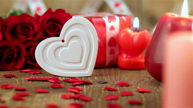 Red roses and heart shape on wooden background video