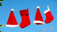 Red Santa hats and Christmas stocking hanging on tropical beach video