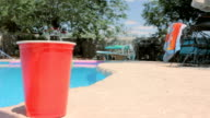 Red Solo Cup Sits Poolside Next to a Swimming Pool video