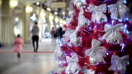 Red spruce in silver bows. New Year's and abstract blurred shopping mall background with Christmas tree decorations video