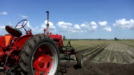 Red tractor and field. Timelapse clouds. video