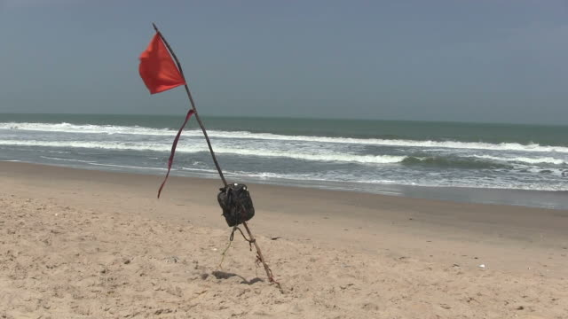 Red warning flag flying on a beach. video