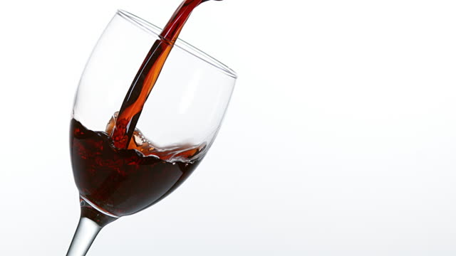 Red Wine being poured into Glass, against White Background, Slow motion 4K video