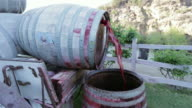 Red wine falling from one barrel to the other video