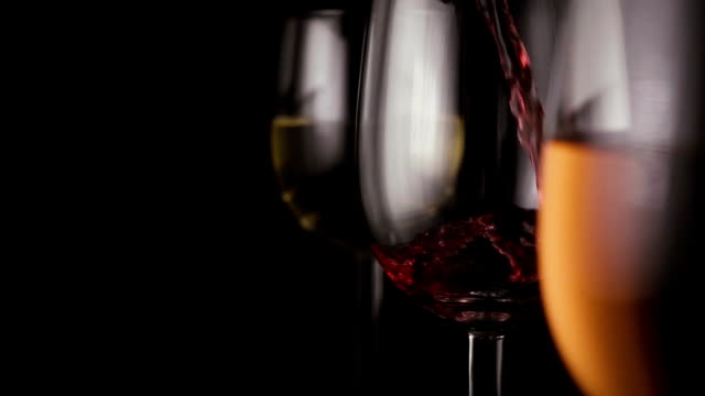Red wine is poured into one of the three glasses video