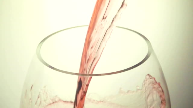 Red wine on a white background slow motion video