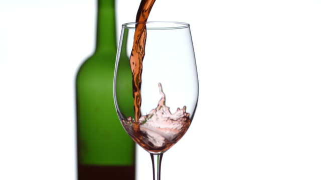 Red wine pouring in slow motion with bottle in background video