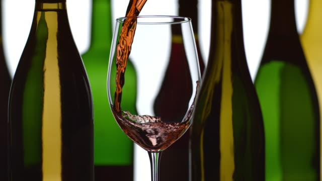 Red wine pouring in slow motion with bottles in background video