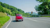 Red zastava car passing the bus stop and cross roads video