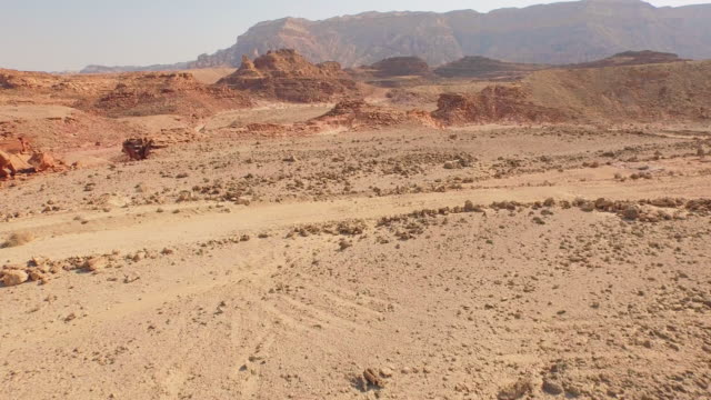 Reddish boulder lying in the middle of desert. Aerial view video