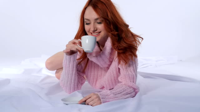 Red-haired girl drinking coffee lying on the bed video