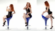Red-haired girl posing in studio on a blue chair video