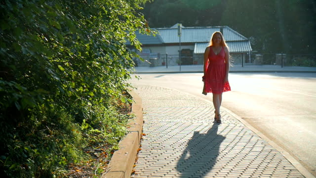 Red-haired girl walking through the city at sunset video