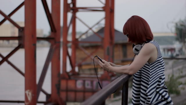 red-haired woman by the bridge chatting online and smileing video