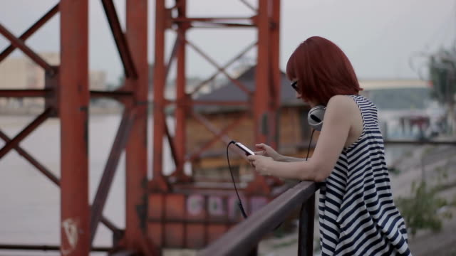 red-haired woman by the bridge chatting online video