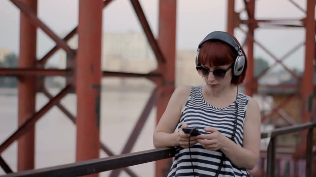 red-haired woman by the bridge listening music in earphones video
