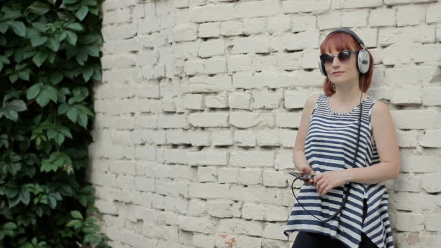 red-haired woman by the wall wearing headphones video