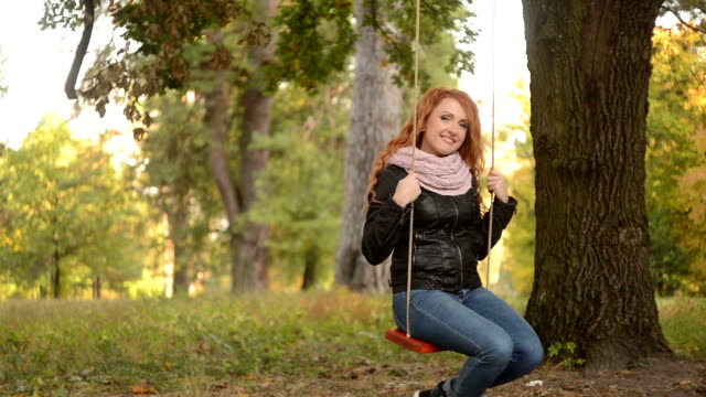 red-haired woman riding on a swing in the park video
