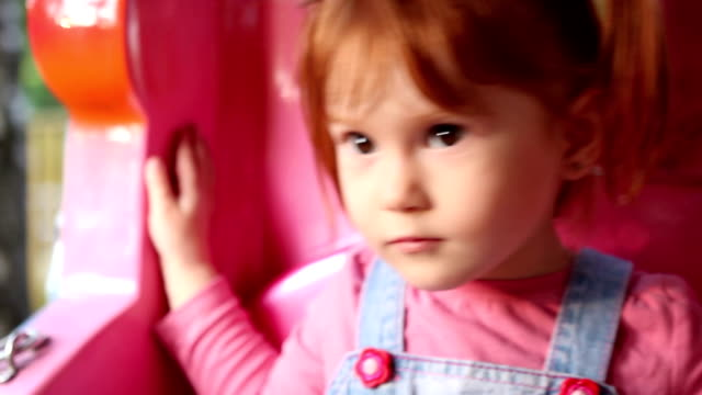 Redhead baby girl child riding toy train in luna park video