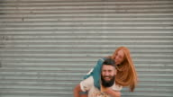 Redhead girl laughing loudly while hipster boyfriend piggyback video