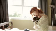 Redhead woman sitting in bed holding her small dog video